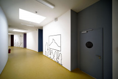 Význam středové zokruhované chodby posilují pravidelně řazené světlíky, dodávající pocit vertikálně neukončeného prostoru