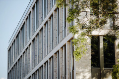 Prosklená fasáda s cihelným obkladem navazuje na některé stavby z první poloviny 20. století ve městě