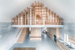 Interiér domu korunovaný obloukem v hřebeni střechy je jedním spojitým prostorem rozděleným vzdušnou knihovnou