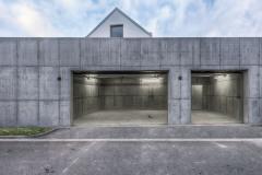 Pohledový beton garáže je doplněn o pohledové pečlivě rozmístěné instalace