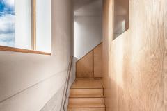 Hladký povrch podlah a nábytku v kontrastu s režným zdivem