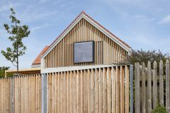 Ve štítech nové sedlové střechy jsou velká okna, která stíní a částečně zakrývají modřínové lamely