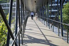 Most, vystupující ze zeleného svahu jako stvol, je koncipovaný jako otevřený visutý chodník navlečený do lehkého rukávce síťové treláže porostlé popínavou vegetací
