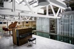 Pro prezentaci klavírů a pianin byla zvolena přístavba u hlavního showroomu na místě původního plechového přístřešku. Přístavbě dominuje celoprosklená plocha severního a východního fasádního pláště.