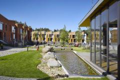 Mezi domy vzniklo náměstí s komponovanou zelení, sochařskou výbavou, vodní plochou a lavičkami. Součástí parku je také prosklená klubovna.