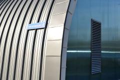 Na obloukové části vnější stěny a střešním plášti jsou lakované hliníkové profily, další část fasády kryjí plechové kazety a polykarbonátový obklad
